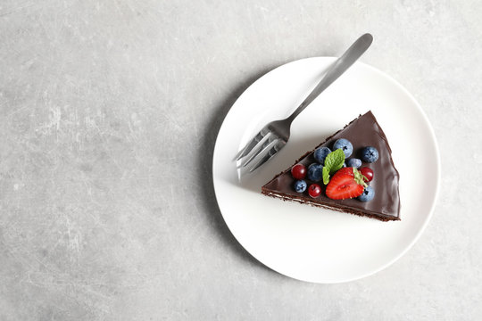 Plate with slice of chocolate sponge berry cake on grey background, top view