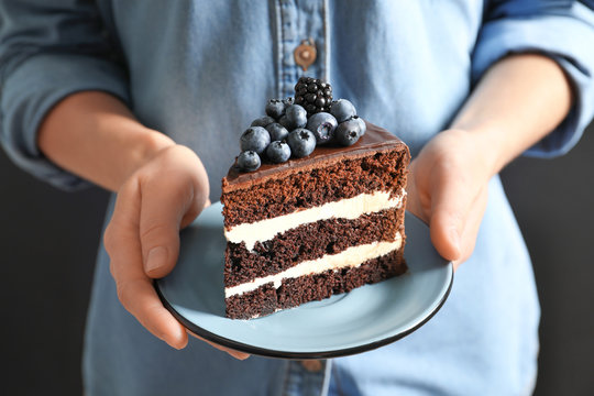 Woman holding plate with slice of chocolate sponge berry cake, closeup