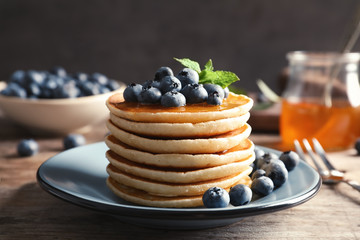 Plate with pancakes and berries on wooden table