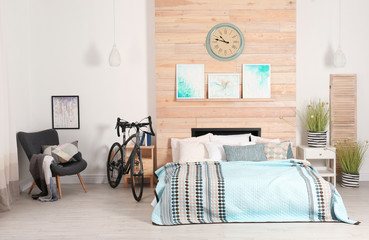 Modern apartment interior with bicycle near bed