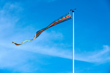 A flag of Åland Islands, Finland against a blue sky.