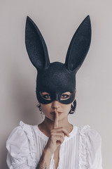 young woman in bunny mask showing quiet sign