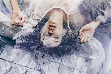 close up portrait of beautiful woman lying on water with fabric. Fashion concept