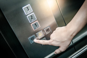 Male forefinger pressing on the open door button in elevator (lift). Mechanical engineering concept