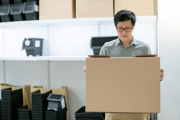 Young Asian man carrying cardboard box choosing what to buy. Warehouse shopping concept