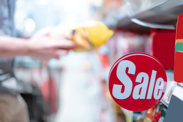 Red sale label on product shelf in supermarket with blurred male hand shopper choosing food package in the background. shopping lifestyle in grocery store concept