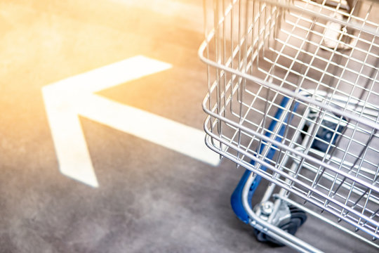 Shopping cart (trolley) over go forward arrowhead sign on the floor in supermarket or grocery store. Shopping lifestyle concept