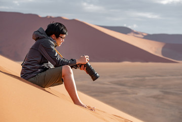Young Asian man traveler and photographer looking at photo disply on camera sitting on sand dune in Namib desert of Namibia, Africa. Travel photography concept
