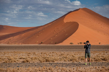 Young male traveler and photographer taking photo in Namib desert with orange sand dune in the background. Travel Namibia, Africa. Photography concept