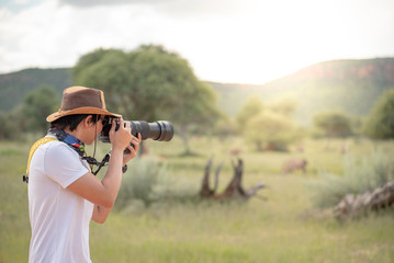 Young man traveler and photographer taking photo of wildlife animal in African safari. Wildlife photography concept