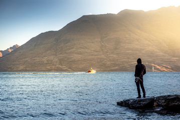 Male traveler standing on the rock looking at mountain scenery during sunset at Lake Wakatipu in Queenstown, South Island, New Zealand. Travel concept