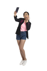 Cute asian girl in casual cloth holding mobile phone and take selfie in studio.
