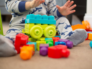 toddler playing with toy building blocks