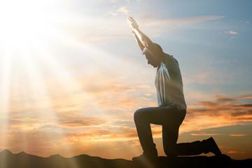 Man Kneeling And Praying At Sunset