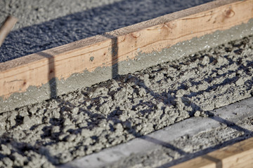Wet Cement with a 2x4 wood to level it