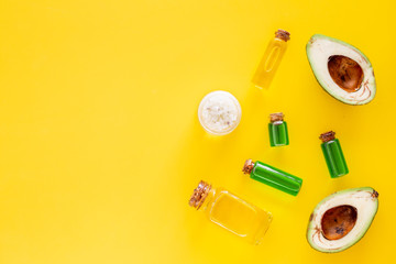 Cosmetics for skin care. Avocado oil near half of avocado on yellow background top view copy space