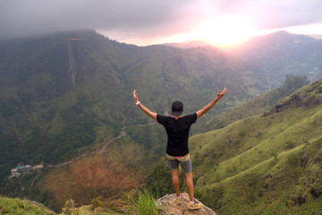 Carefree happy man enjoying nature and sunrise standing on top of mountain cliff