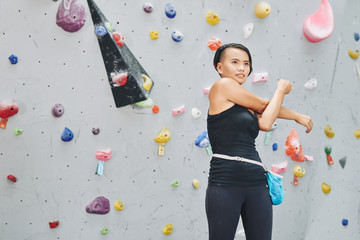 Pretty Vietnamese woman warming-up before bouldering on artificial wall