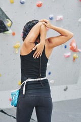 Rear view of sporty young woman stretching arms before climbing