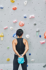 Female climber taking chalk powder from sack on her waist
