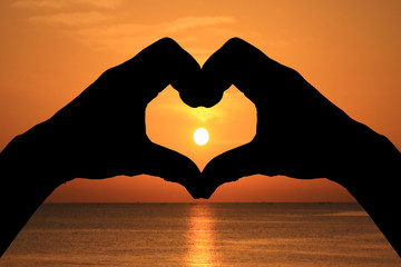 silhouette heart shape with hands on sunset