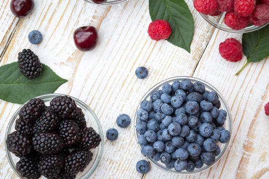 Raspberries, blackberries, cherries and blueberries in a glass bowls on wooden background. Seasonal fruits