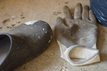 Graue Arbeitshandschuhe liegen auf Betonboden neben mit Wandfarbe bekleckerten Schuhen