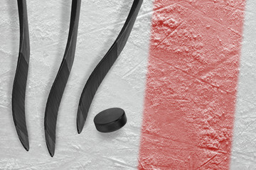 Three hockey sticks, a puck and a fragment of the ice arena with a red line
