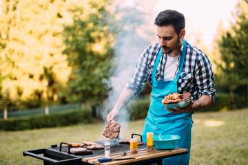 Happy male preparing bbq meat