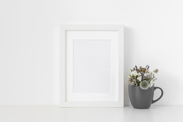 Minimal white A5 portrait frame mockup with small bouquet of dried flowers in gray mug on white wall background. Empty frame, poster mock up for presentation design. Template frame for text, lettering