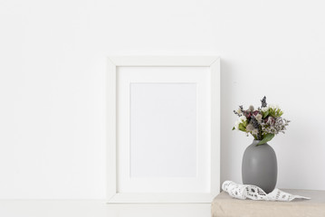 White a5 portrait frame mockup with dried field wild flowers in vase, vintage lace and book on white wall background. Empty frame, poster mock up for presentation design. Template frame for text