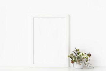 White a4 portrait frame mockup with dried field wild flowers in small white pot on white wall background. Empty frame, poster mock up for presentation design. Template frame for text, lettering