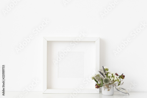 087563c8b012 White square portrait frame mockup with small bouquet of dried flowers in  small white pot on white wall background. Empty frame