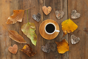 top view image of coffee cup over wooden table and dry autumn leaves.