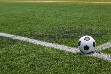 soccer ball on the white line on green soccer field grass