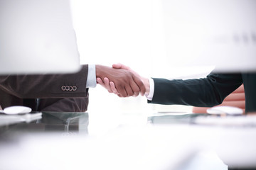background image of handshake of business partners above the Desk