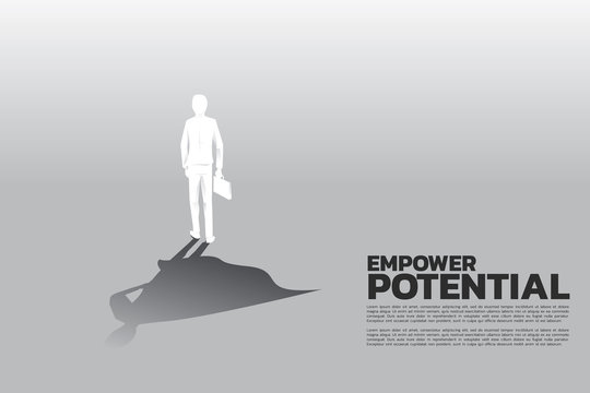 Silhouette of businessman with briefcase and his shadow of superhero.concept of empower potential and human resource management
