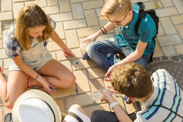Communication and recreation group of 4 children teenagers. Friends play a board game, throwing dice