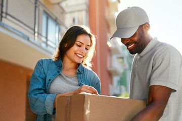 Courier Delivery Service. Man Delivering Package To Woman