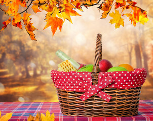 Wooden table with autumn leaves and picnic basket