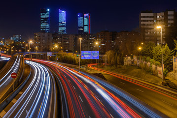 Fotobehang Nacht snelweg Night long exposure photography at M30 highway with Madrid skyline (Four towers business area) as background, Spain