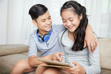 Smiling kid showing funny picture on tablet computer to his sister