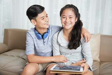 Laughing hugging brother and sister resting on sofa with digital tablet