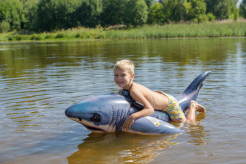 little boy swimming in the river on an inflatable shark
