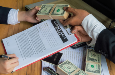 Businessmen use money to bribe other people in exchange for signing contracts, with blurred soft background to Dark business concept