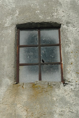 Old dirty cast-iron framed window in a concrete building.