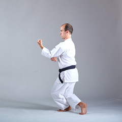 An adult sportsman trains formal karate exercises against a gray background