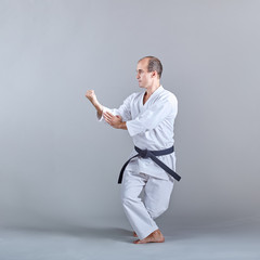 In a low stand, an athlete trains a formal karate exercise