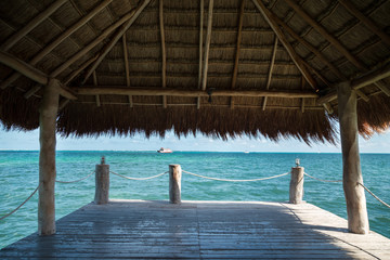 View of the Caribbean from a pier with a grass roof.