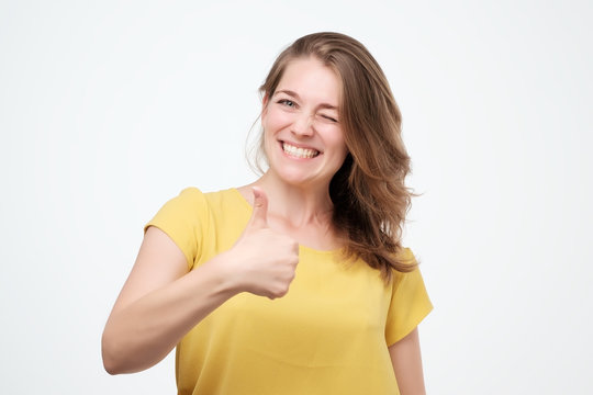 Happy young woman giving thumbs up on white background